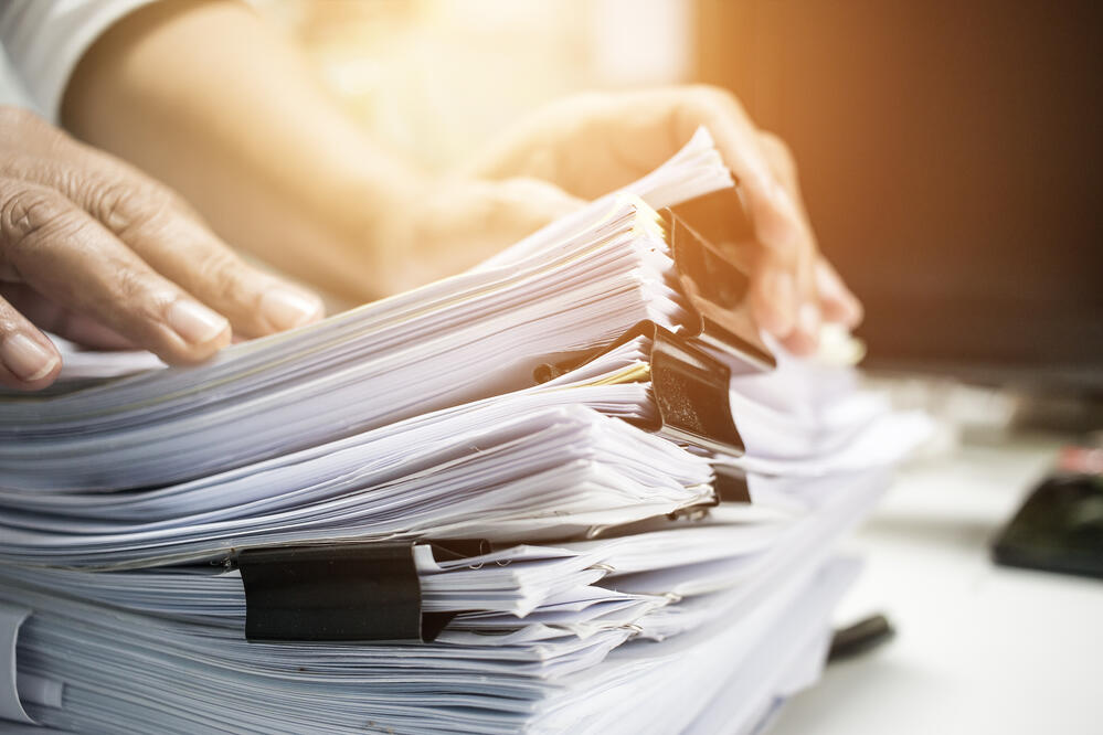 person managing stack of files and reports
